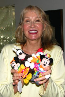 Alyja holds dolls wearing her costumes she designed for a parade. These were sold in Tokyo Disneyland.